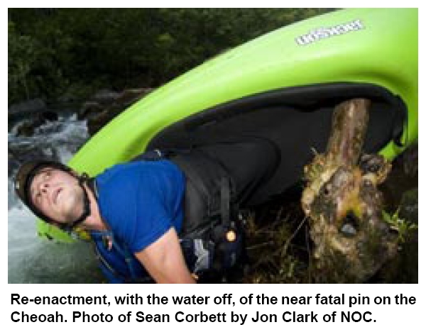 Kayaker upside down pinned by a log